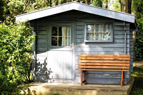 abri de jardin en bois clair avec un banc devant