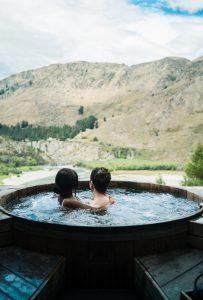deux personnes dans un spa en bois face à la nature